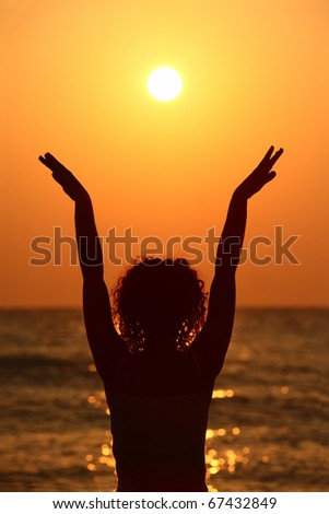 beautiful young woman standing on beach, watching sunset, raises her hands - stock photo
