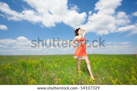 Beautiful young woman standing on field enjoying wind wave - stock photo
