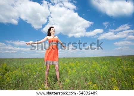 Beautiful young woman standing on field enjoying wind wave