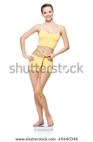 Beautiful young woman standing on scales and measuring her slim waist with measure type, on white background