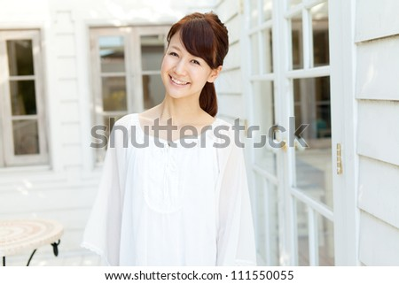 Beautiful young woman standing on terrace. Portrait of asian.
