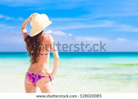 Beautiful young woman standing on the beach enjoying the sun - stock photo