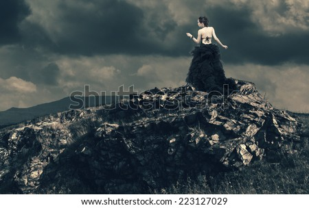 Beautiful young woman standing on the edge of a precipice in stormy weather. - stock photo