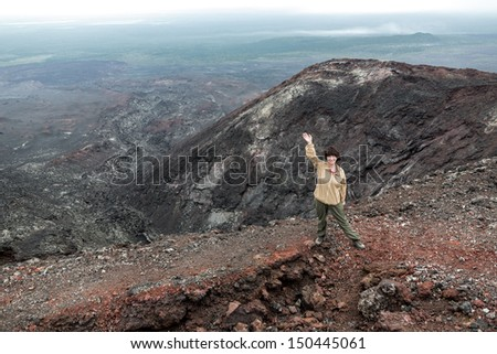 Beautiful young woman standing on the edge of the 2nd crater of the Northern breakthrough 1975 eruption volcano Tolbachik - Kamchatka, Russia - stock photo
