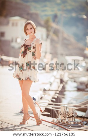 Beautiful young woman standing on the pier - stock photo