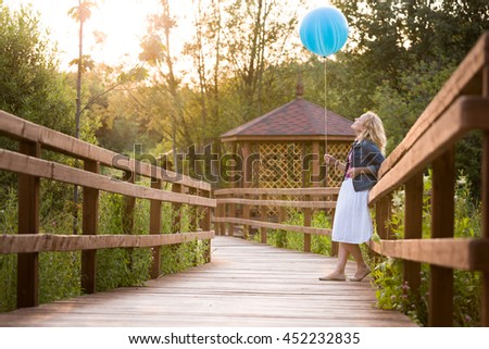 Beautiful young woman standing on wooden bridge and holding big blue balloon on the sunset in the park. Birthday girl