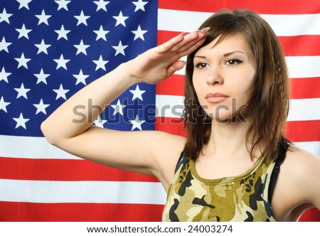 beautiful young woman standing opposite an American flag and wearing camouflage salutes - stock photo