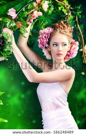 Beautiful young woman standing under an arch of flowers and overgrown loach. Magic of the spring. - stock photo