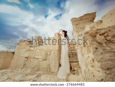 beautiful young Woman standing wearing White and Gold Greek Costume inside ancient ruins.
