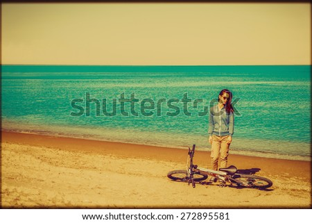 Beautiful young woman standing with a bicycle on beach. Image with vintage color effect and rectangular frame - stock photo