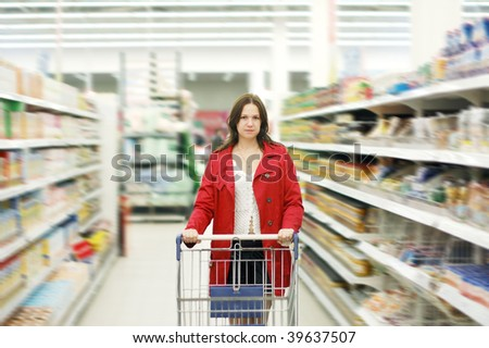 Beautiful young woman standing with a trolley at a supermarket - stock photo