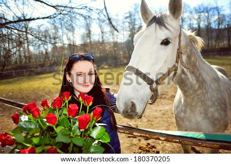 Beautiful young woman standing with bunch of roses before white horse - stock photo