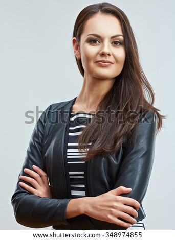 Beautiful young woman standing with crossed arms. Smiling girl in leather jacket. - stock photo