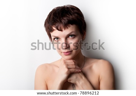Beautiful young woman standing with her hands folded - stock photo