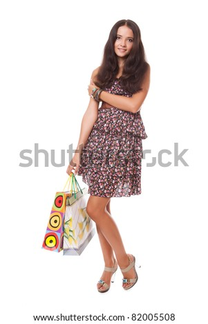 beautiful young woman standing with shopping bags over white background - stock photo