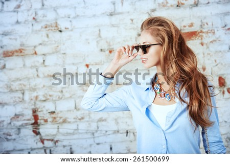 Beautiful young woman stands near the old brick wall in the city. - stock photo