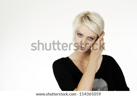 Beautiful young woman staring at the camera with a serious expression and her hand raised to her short trendy blond hair holding her fringe clear of her face, isolated on white with copyspace