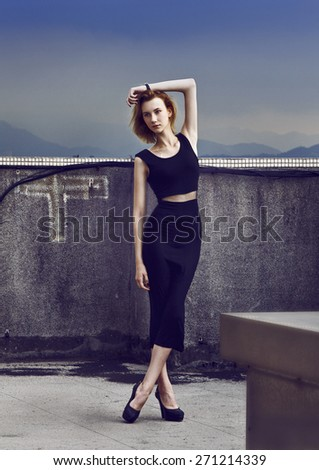 Beautiful young woman staying on the rooftop in black dress. Fashion pose focus on the long legs. Developed from RAW. Retouched with special care and attention. - stock photo
