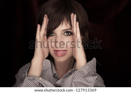 Beautiful Young Woman Sticking tongue out at camera.  Great detail in mouth and eyes. - stock photo
