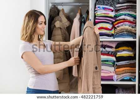 Beautiful young woman storing her clothes in closet.