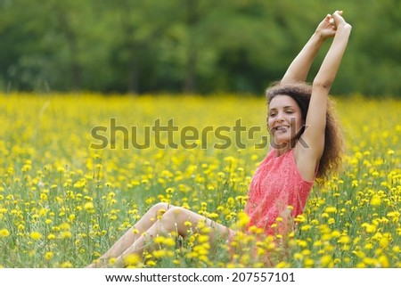 Beautiful young woman stretching her arms high in the air with a smile of pleasure and satisfaction as she sits in a rural meadow full of colorful yellow flowers, with copyspace - stock photo