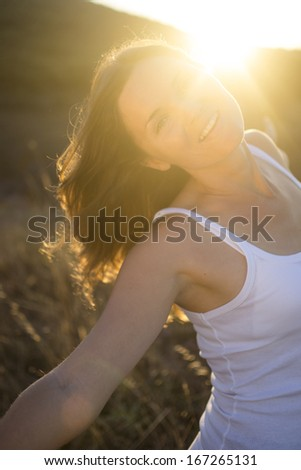 Beautiful young woman stretching her arms joyfully praising the beauty of Life. - stock photo