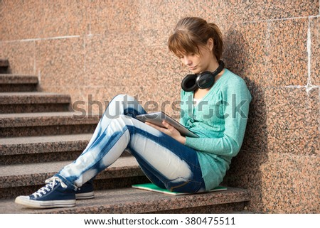 Beautiful young woman student with note pad and headphones. Outdoor student. - stock photo