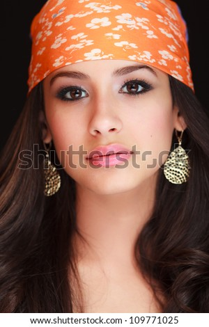 Beautiful young woman studio portrait wearing a colorful bandana on a black background. - stock photo