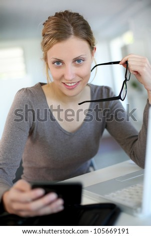 Beautiful young woman studying at home on laptop - stock photo