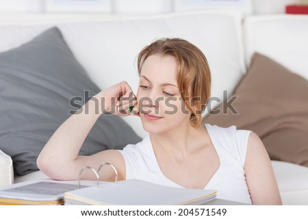 Beautiful young woman studying at home sitting leaning back against the sofa reading her notes in a large binder - stock photo