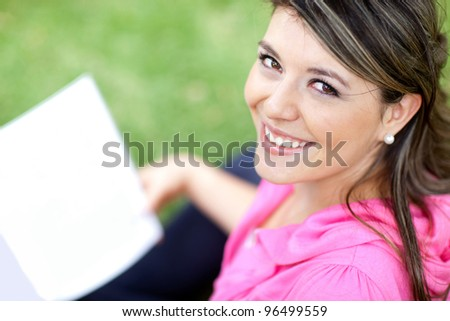 Beautiful young woman studying with a book at the park - stock photo