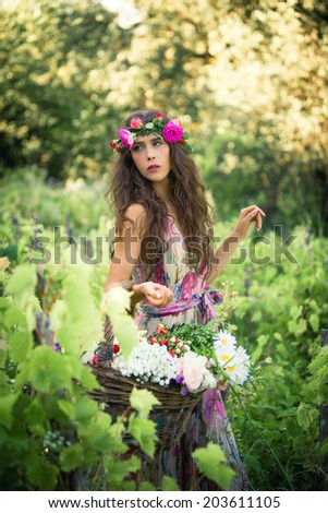 beautiful young woman summer portrait with wreath of flowers in hair and basket of flowers in hand outdoor shot - stock photo