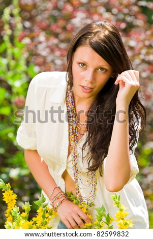 Beautiful young woman sunny garden care yellow flower portrait