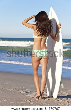 Beautiful young woman surfer girl in bikini with white surfboard at a beach