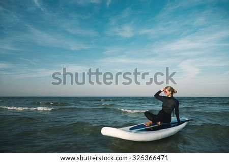 Beautiful young woman surfing lies on stand up paddle board at exotic vacation at deep blue sea - stock photo
