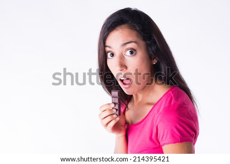 beautiful young woman surprised caught eating chocolate with a guilty attitude  - stock photo