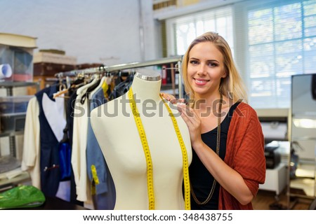 Beautiful young woman tailor with mannequin in her workshop