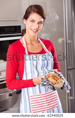 Beautiful young woman taking a fresh cake out of the oven - stock photo