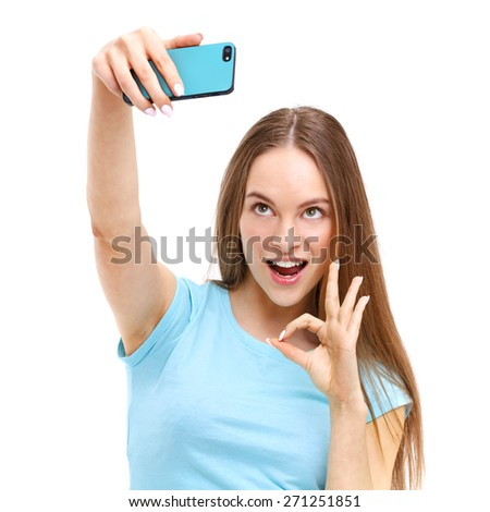Beautiful young woman taking a picture of herself with her camera phone - isolated on white background. - stock photo