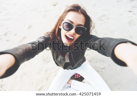 Beautiful, young woman taking a selfie outdoors on the sand - stock photo