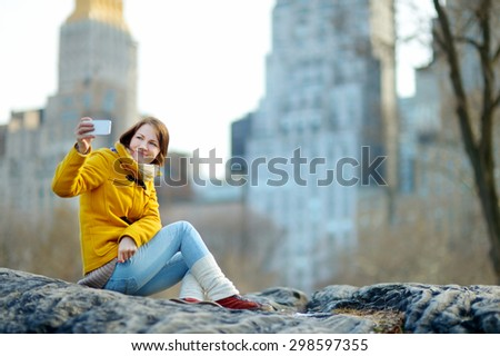 Beautiful young woman taking a selfie while sitting on a rock in Central Park, New York - stock photo
