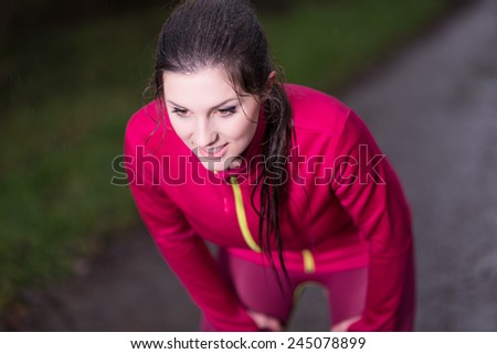 Beautiful young woman taking a short break while jogging on a rainy day - stock photo