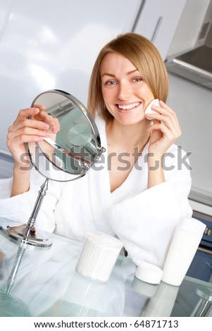 beautiful young woman taking care of her face at home - stock photo