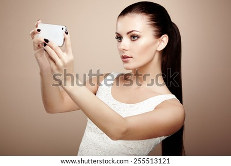 Beautiful young woman taking selfie. Girl photographing herself with phone. Beauty fashion. Eyelashes. Cosmetic Eyeshadow - stock photo