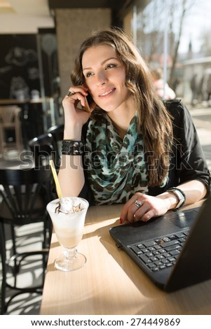 Beautiful young woman talking on a mobile phone, having a coffe break in a local internet cafe. - stock photo