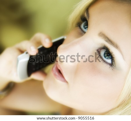 Beautiful young woman talking on cell phone - stock photo