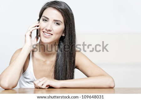 Beautiful young woman talking on her mobile phone at home - stock photo