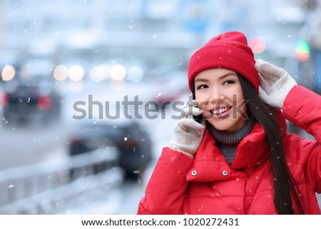 Beautiful young woman talking on mobile phone outdoors on winter day