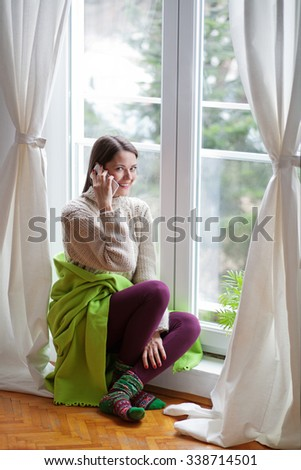 Beautiful young woman talking on phone while sitting by the window - stock photo