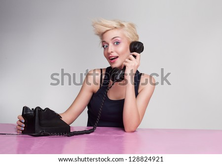 beautiful young woman talking on the phone and looking at camera - stock photo